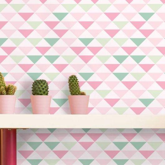Papel de parede geométrico rosa, verde e branco com prateleira com cactos na frente.