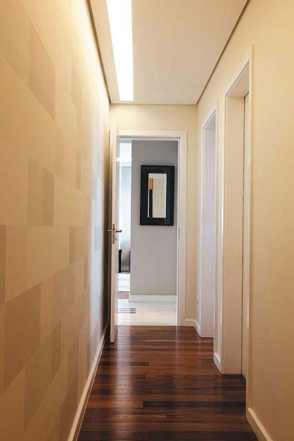 Corredor com papel de parede geométrico com quadrados com diferentes tons de beje.