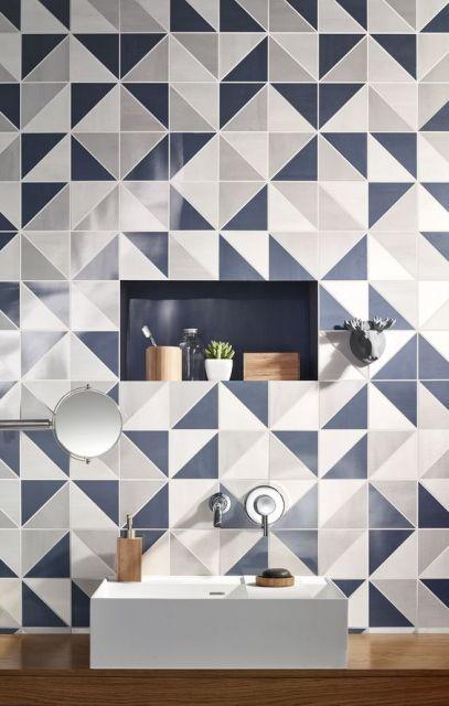 Papel de parede geométrico com triângulos brancos, azuis e cinzas em banheiro.