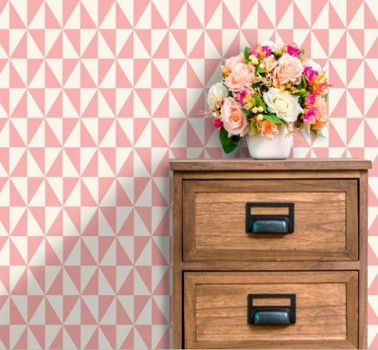 Móvel de madeira com vaso de flor em cima e papel de parede com triângulos brancos e rosas.