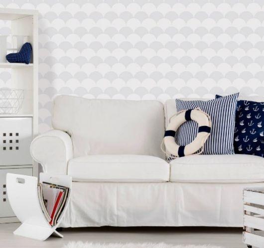 Sofá claro com almofadas azuis que remetem ao tema náutico e papel de parede geométrico cinza.