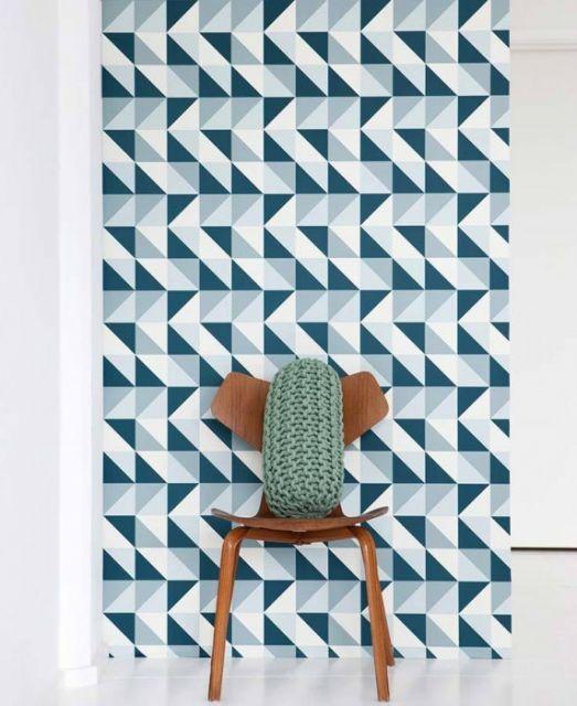 Papel de parede com triângulos brancos, azul claro e escuro, atrás de uma cadeira com almofada.