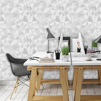 Escritório com papel de parede com triângulos cinza e branco.