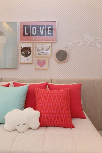 Papel de parede rosa com quadros em cima da cabeceira da cama.