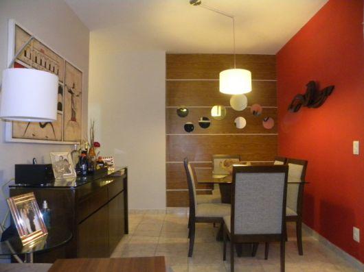 papel de parede de madeira em sala de jantar com parede oposta vermelha
