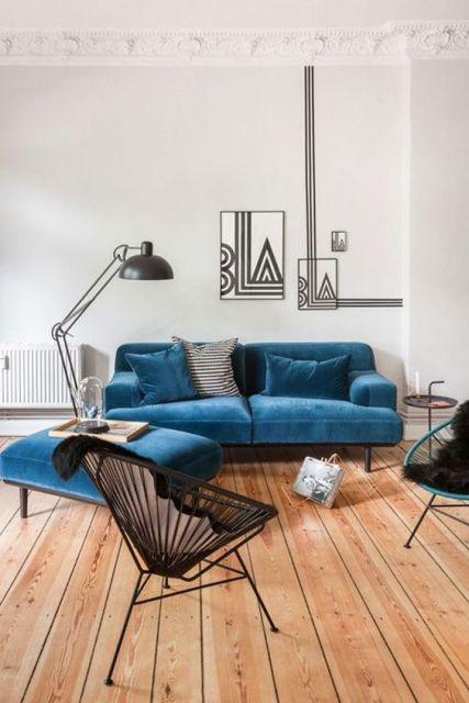 sofá de veludo azul com apoio de pé em ambiente minimalista