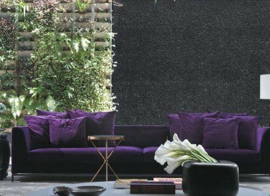 sofá de veludo roxo em sala com jardim vertical ao fundo