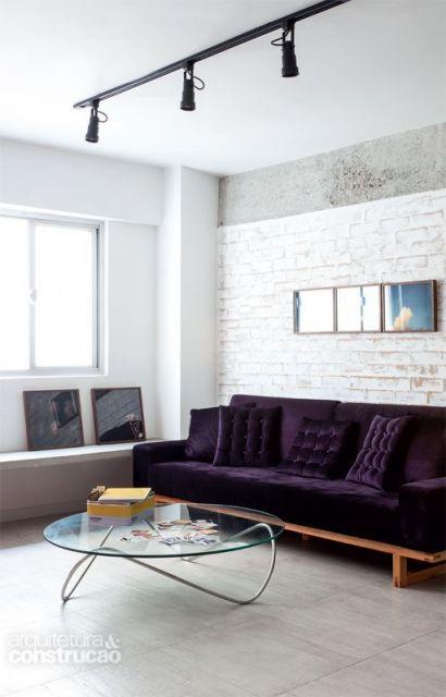 sofá de veludo roxo com almofadas de botões aparentes