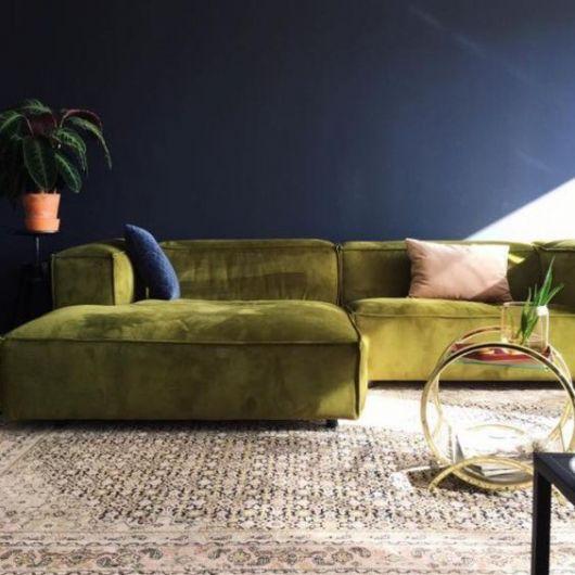 sofá de veludo verde-musgo com parede azul-marinha ao fundo