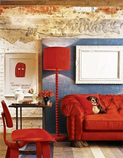 sofá de veludo vermelho em ambiente com parede de tijolos