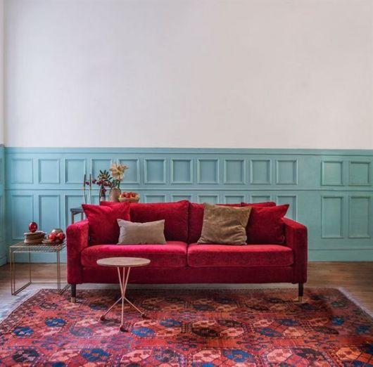 sofá de veludo vermelho com parede azul clara