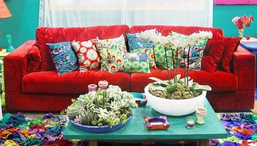 sofá de veludo vermelho com almofadas e móveis azuis