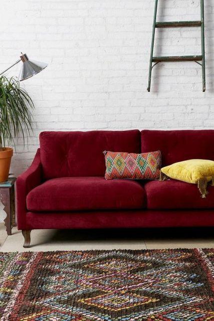 sofá de veludo bordô com parede branca ao fundo