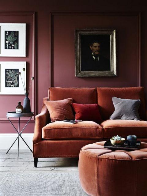 sofá de veludo marrom com parede vinho ao fundo