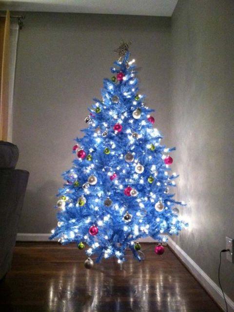 árvore de natal azul com pisca-pisca muito forte no canto de uma casa