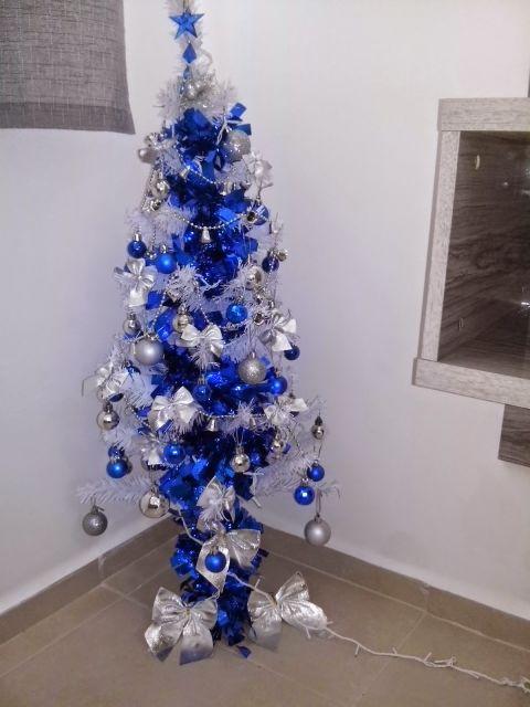 árvore de natal azul enfeitada com bolas pratas e azuis e uma estrela no topo