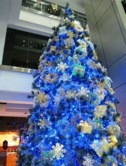 árvore de natal azul enfeitada com caixas de presente e flocos de neve fotografada de baixo para cima