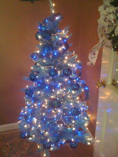 árvore de natal azul pequena com bolas azuis penduradas e pisca-pisca prata