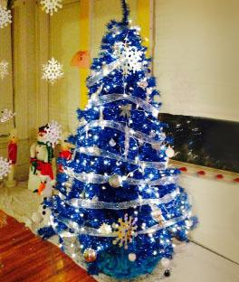 árvore de natal azul enfeitada com um laço e bolas na cor prata