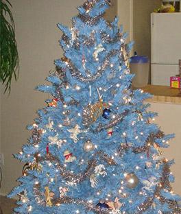 árvore de natal azul-bebê com muitos enfeites, alguns prata e outros dourados