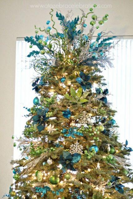 árvore de natal azul enfeitada com muitos enfeites dourados