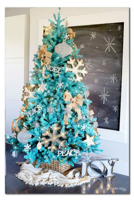 árvore de natal azul com enfeites de laço e floco de neve dourados ao seu redor