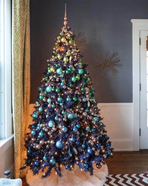árvore de natal azul enfeitada com bolas de diversas cores, que se tornam douradas no topo