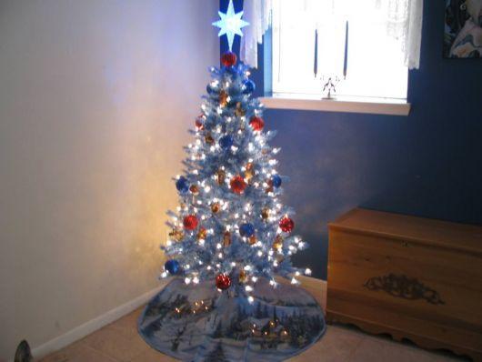 árvore de natal azul enfeitada com pisca-pisca e bolas vermelhas, azuis e douradas