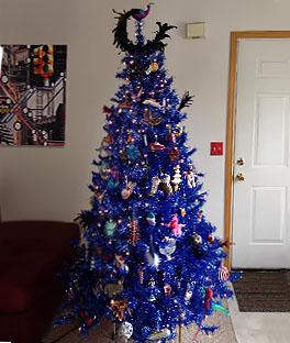 árvore de natal azul com muitos enfeites de várias cores diferentes