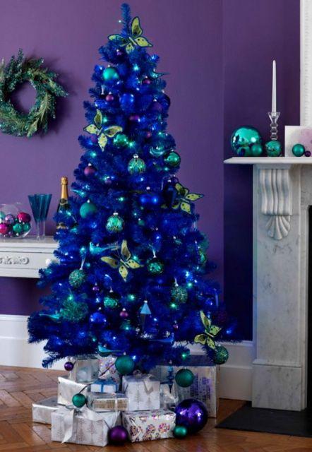 árvore de natal azul com várias bolas verdes penduradas em frente a uma parede roxa