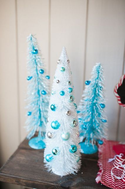 três árvores de natal azuis pequenas em cima de uma mesa