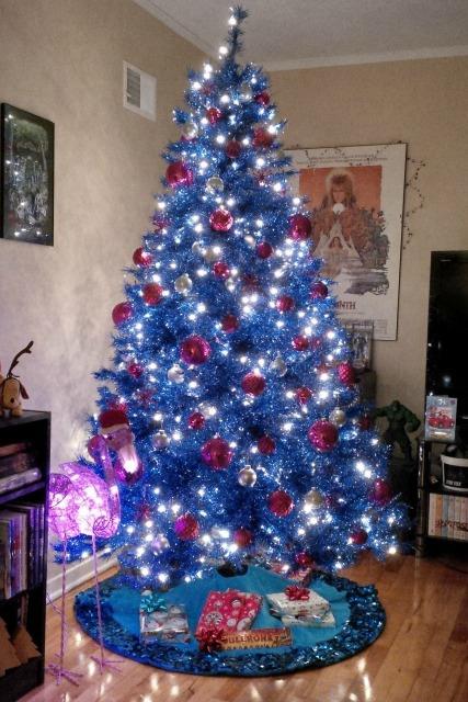 árvore de natal azul com pisca-pisca muito forte e bolas vermelhas e brancas