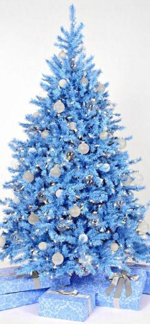 árvore de natal azul com presentes próximos a ela e bolas brancas penduradas