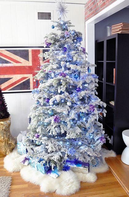 árvore de natal azul enfeitada com neve em suas folhas e presentes próximos a ela