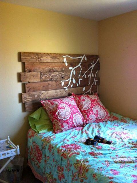 cabeceira de pallets que dá suporte a uma cama no canto do quarto e tem galhos de árvore desenhados sobre ela