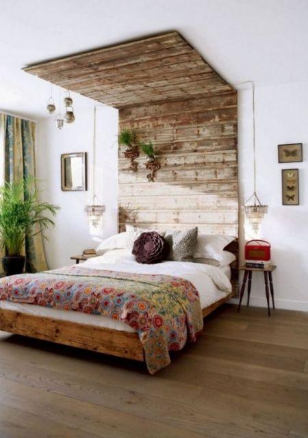Cabeceira de palletes que se estende verticalmente até o fim da parede e emenda no teto, cobrindo parte dele