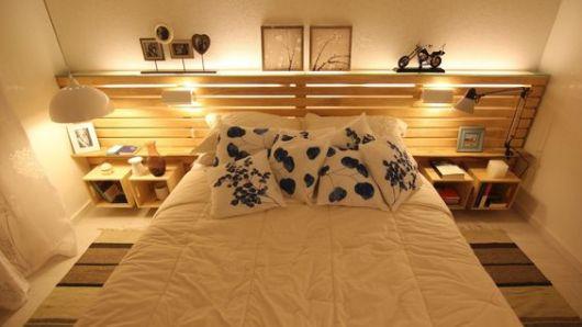 Cabeceira de pallets com pequenos compartimentos e lâmpadas em sua extensão