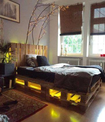 Cama com a base e a cabeceira feita de pallets. A base é iluminada por lâmpadas amarelas.