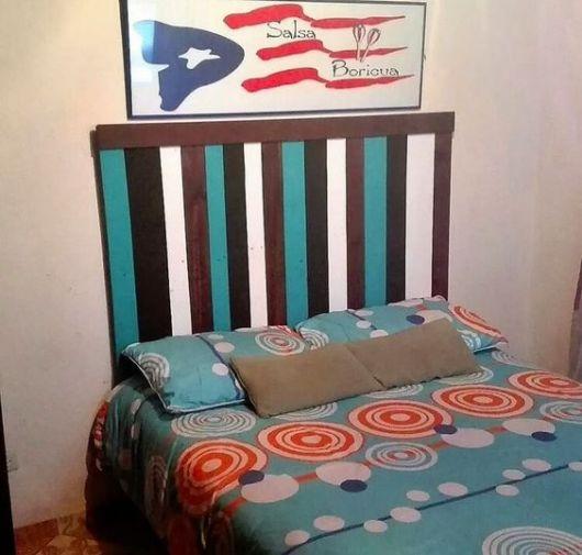 cabeceira de pallets pintada de azul, preto, branco e marrom abaixo de uma quadro