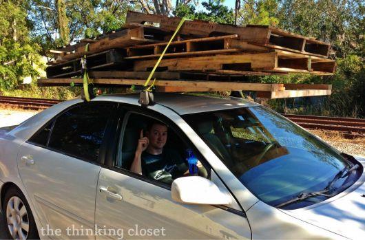 carro carregando diversos paletes com o suporte de uma corda em sua parte superior