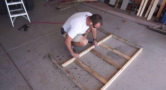 Homem montando a base de uma cabeceira de pallets