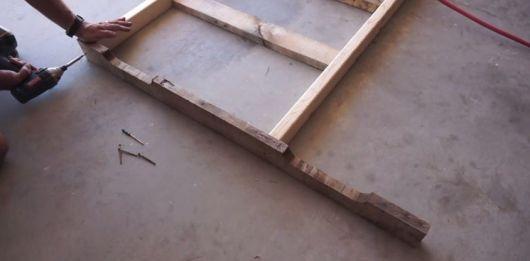 Homem pregando as madeiras que foram a base da cabeceira de pallets