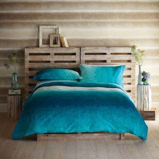 Cabeceira de pallets composta por dois caixotes que dá suporte para uma cama grande com lençol azul