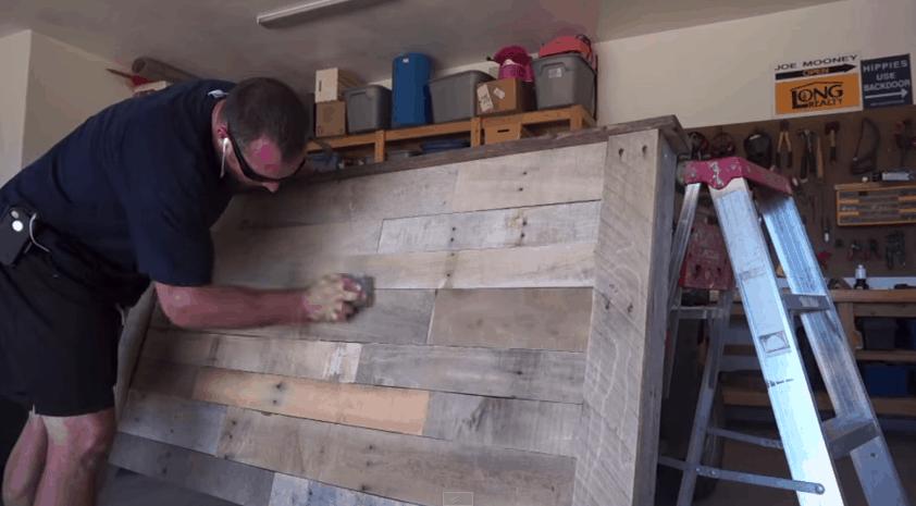 Homem lixando a cabeceira de pallets