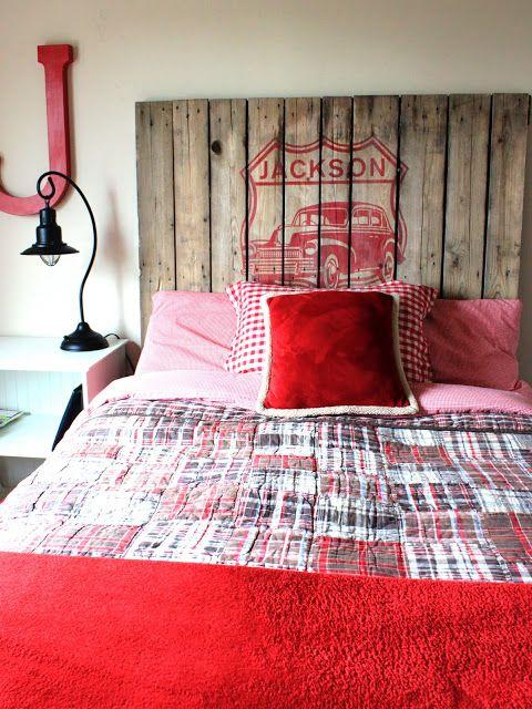 Foto de uma cama vista de frente com cabeceira de pallets onde há o desenho de um carro em vermelho