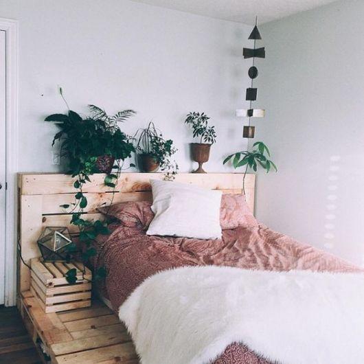 Cabeceira de pallets com vários vasos de plantas apoiados sobre ela
