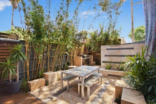 Foto de um deck de pallets com uma mesa no centro e diversas plantas ao redor
