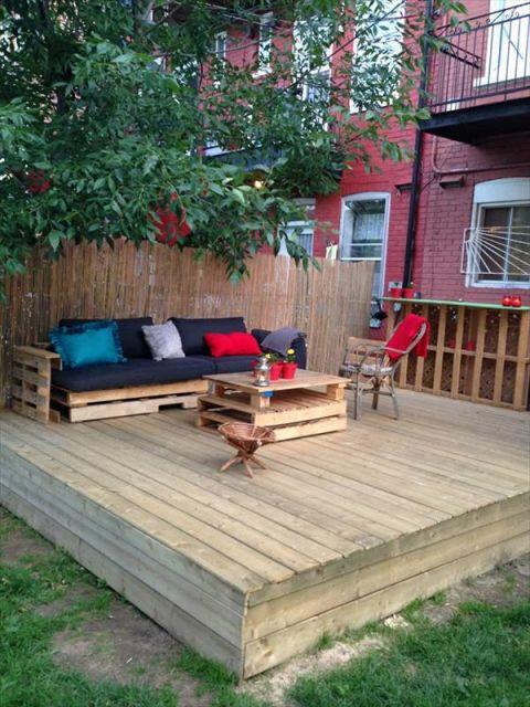 Deck de pallets com uma mesa de centro e uma sofá também feitos com pallets