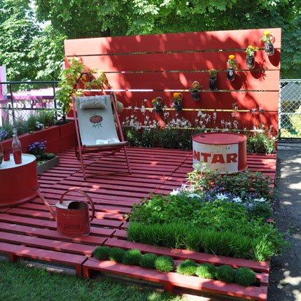 Deck de pallets todo pintado de vermelho com uma cadeira ao centro e uma parede de flores ao fundo
