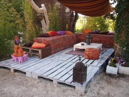 Deck de pallets com um sofá e uma mesa, rodeado por árvores e plantas